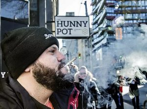 Man Smoking Joint Outside of The Hunny Pot Cannabis Store in Toronto
